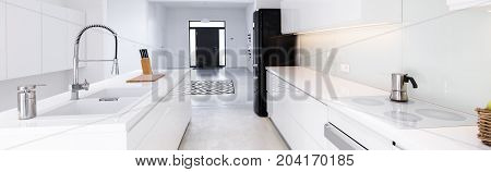 Panorama of high gloss white kitchen with white table tops in modern villa