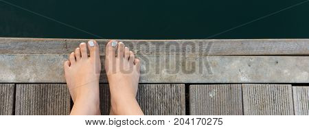 Female Feet On Wooden Deck By The Sea. Bare Woman Feet With White Painted Toenails On Wooden Backgro