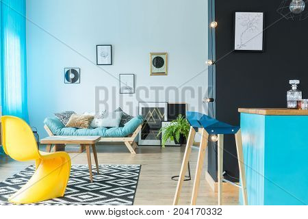 Modern designer barstool at blue kitchen island in colorful living room with yellow chair