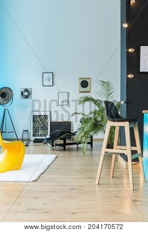 Designer eclectic loft with barstool lamp and posters on white wall and wooden floor