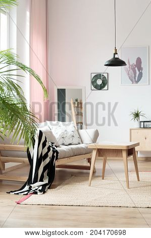 Wooden table on beige carpet near sofa with black and white blanket in cozy room