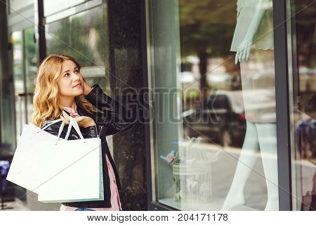 Attractive Young Woman Holding Shopping Bags While Standing In Front Of Shop Window.