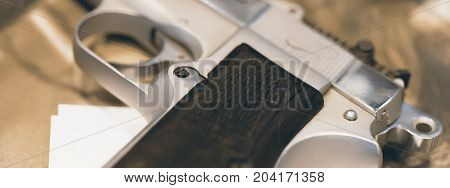 Silver Gun on Wooden Table Close Up