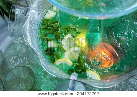 Mojito cocktail. little fountain pours a cocktail on table buffet