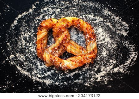 Delicious Fresh pastry on dark background with flour. Sweet pretzels with powdered sugar macro. Beautiful delicious puff pastry