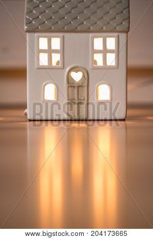 Lit up model home with heart above the door, sat on wooden floor.