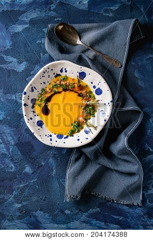 Plate of vegetarian pumpkin carrot soup served with spoon, balsamic sauce and fried onion on textile napkin over dark blue texture background. Top view with space