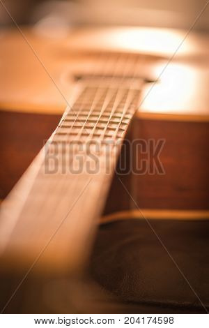 Close up image of frets on acoustic guitar.