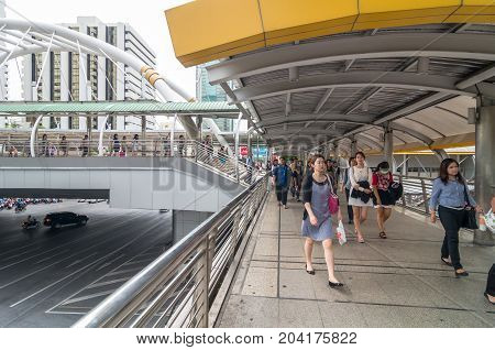 BANGKOK - JUNE 25 2015: Undefined People are walking on the pedestrian bridge which is Bangkok landmark at Chongnonsi SkyBridge at morning for attendance on June 25 2015 in Bangkok Thailand.