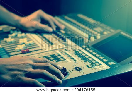 Hand adjusting audio mixer and musical instrument