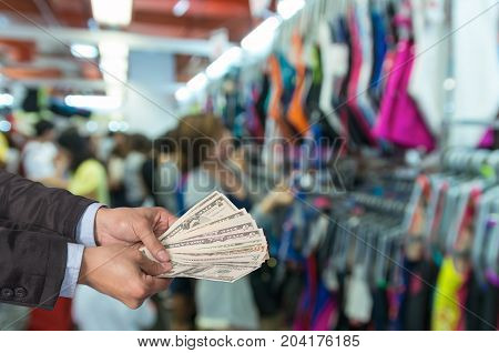 Businessman offered the money on the Abstract blurred photo of store blur with customer choose product bokeh background