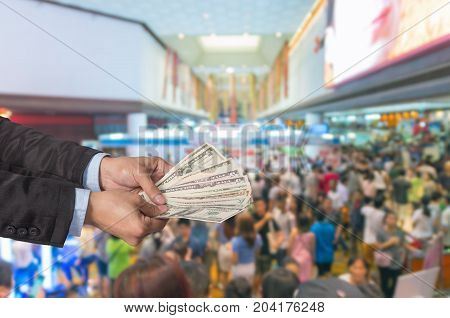 Businessman offered the money on the Abstract blurred photo of store blur with customer bokeh background