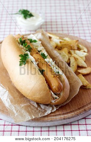 Hot dog with sausage and salad served with french fries mustard and mayonnaise sauce. Rustic style selective focus.
