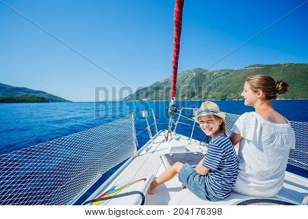 Boy with his sister looking forward on board of sailing yacht on summer cruise. Travel adventure, yachting with child on family vacation.