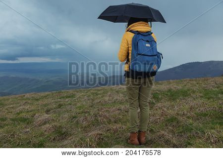 Girl with umbrella watching rain-storm in the distanant landscape.