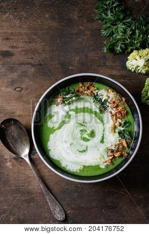 Vegetarian broccoli cream soup served in black bowl with spoon, cream, fried onion, fresh parsley and broccoli over old wooden background. Top view with space. Healthy eating.