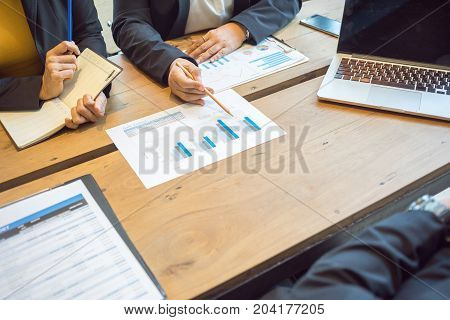Female employees are explaining sales summary report to top management.