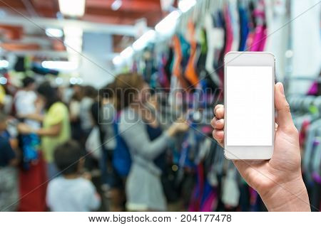 Female hand holding mobile smart phone touch screen on Abstract blurred photo of store blur with customer choose product bokeh background