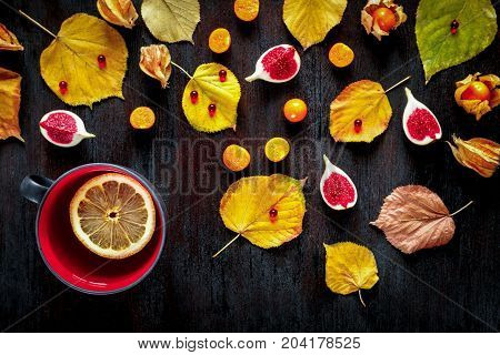 Concept of cold autumn - tae with lemon, leaves on dark wood. Colorfull pattern