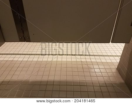 a tiled floor in a bathroom with the stall door