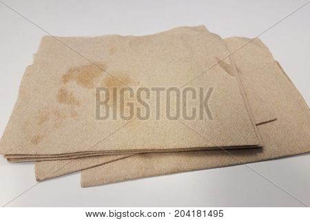 a grease stain on a pile of light brown napkins