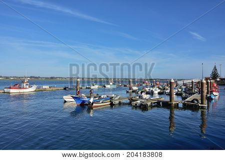 Costa Nova Portugal - June 10 2017: Pier and moored fishing boats in Costa Nova on the Atlantic coast in Beira Litoral Portugal. Popular tourist destination to spend vacation time