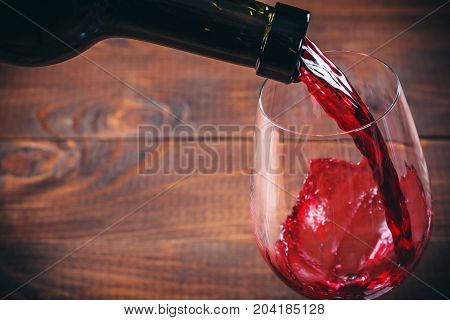 Pouring Red Wine Into The Glass On Wooden Background