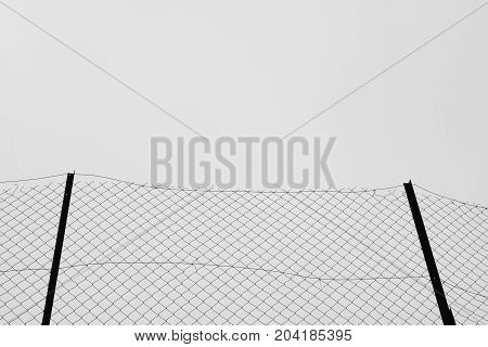 Rusty fence posts iron chain link fencing wire mesh netting background. Black and white.