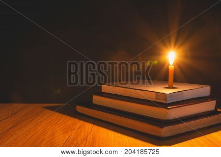 Close-up of burning candle with pile of old book on wooden table. Education concept.