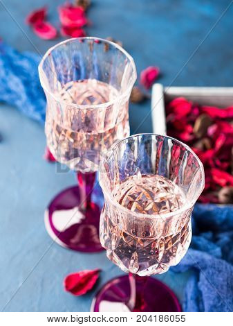 Two Stemmed Glasses With Champagne On Blue