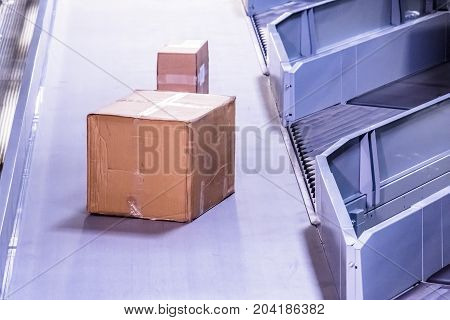 Parcels on belt conveyors with blurred industrial background
