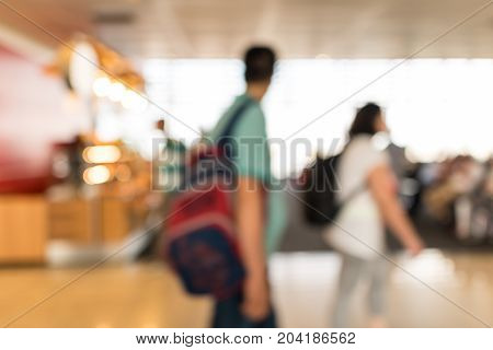 Defocused airport hall with walking travelers. Travel concept.