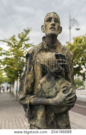 Dublin Ireland - August 7 2017: Great Irish Famine bronze statue set on Custom House Quay along Liffey River in Docklands. One slender male figure. Green trees and gray sky.