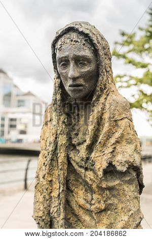 Dublin Ireland - August 7 2017: Great Irish Famine bronze statue set on Custom House Quay along Liffey River in Docklands. One slender female figure. Green trees and gray sky.