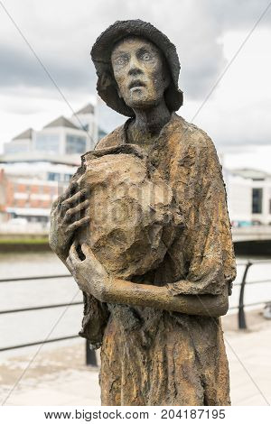 Dublin Ireland - August 7 2017: Great Irish Famine bronze statue set on Custom House Quay along Liffey River in Docklands. One slender male figure.