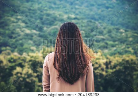 A woman turn back and standing alone with green nature and mountain background