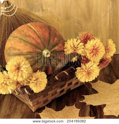 Pumpkin in a wicker basket with flowers and dry leaves. Autumn still life. Old photo filter