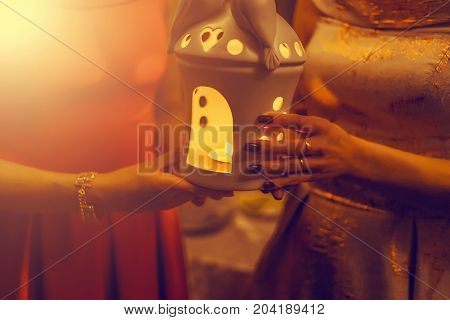 Religious Concept. Two Females Hands Holding A Burning Candle In Candlestick. Vintage Tone