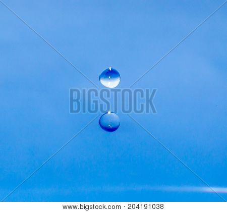 a drop of water falling in blue water. macro