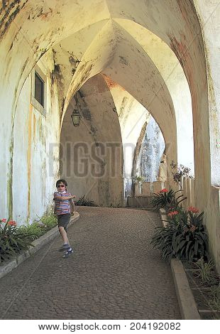 Sintra, Portugal - April 29, 2014: Boy running in the ancient corridor of Pena Palace in Sintra, Portugal