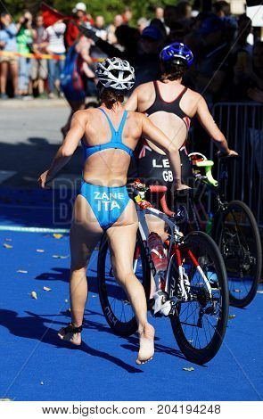 STOCKHOLM - AUG 26 2017: Back of female triathlete Ilaria Zane (ITA) and competitors running with cycle in the transition zone in the Women's ITU World Triathlon series event August 26 2017 in Stockholm Sweden