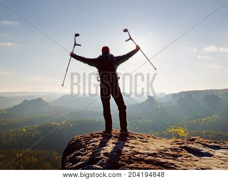 Tourist With Medicine Crutch Above Head Achieve Mountain Peak. Hurt Backpacker With Broken Leg