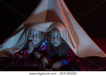 Girls With Scared Faces Lie Under Pink Blanket Tent