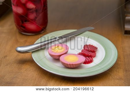 Sliced organic pickled beet eggs on wooden table