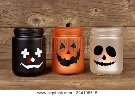 Mason Jar Halloween Candle Holders Against An Old Wood Background