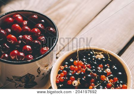 Fresh cherries and currant on rustic wooden table.