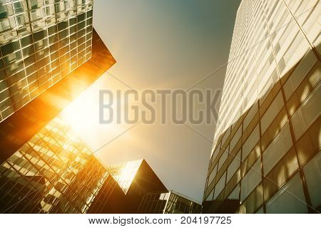 Skyscraper Glass Facades On A Bright Sunny Day With Sunbeams In The Blue Sky. Modern Buildings In Pa