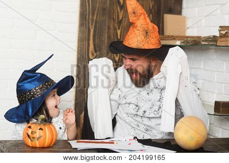 Man and boy on wooden and white brick background. Man and kid with scary and scared faces in hats play with pumpkins. Witcher and little magician make Halloween decor. Halloween and holiday concept