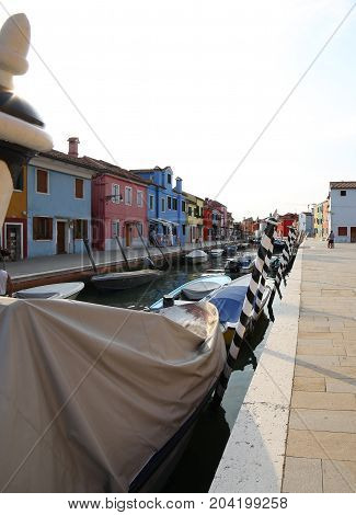Boats Moored In The Navigable Canal Of Burano Island Near Venice