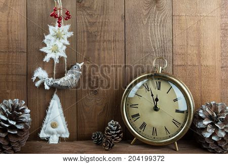 Pretty handmade fabric Christmas decorations in a traditional style hanging on a wooden background. Cute decorated bird stars and Christmas tree with red berries pine cones and a vintage clock about to reach 12 o'clock time for Christmas. Copy space.